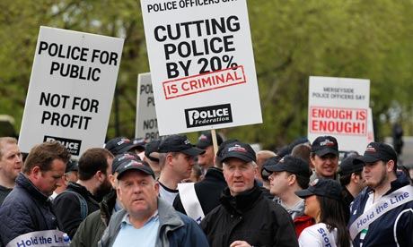 Police officers protesting against budget cuts join public sector workers striking over pensions